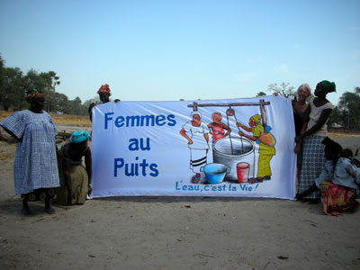 Village women in their garden with our banner, Women at the Well, Water is Life