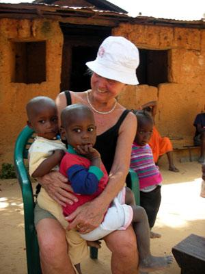 Edie holding village children