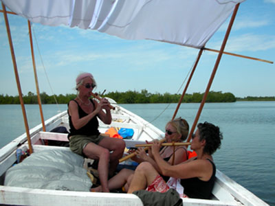 Catherine, Edie, and Vijali playing music in their pirogue, fishing canoe